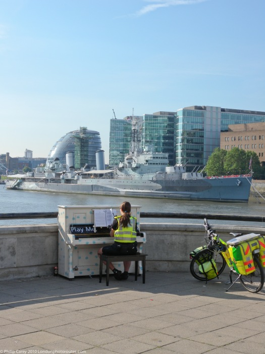 Paramedic playing piano overlooking HMS Belfast