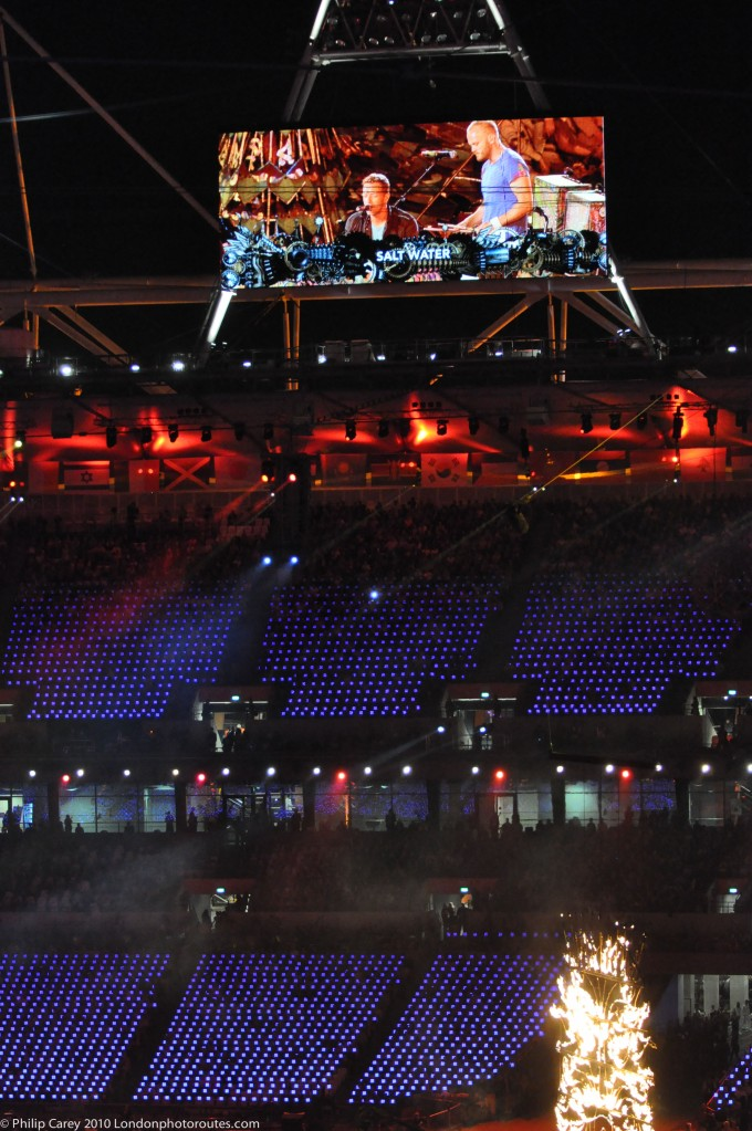 Coldplay on screen 'Festival of the Flame' concert.