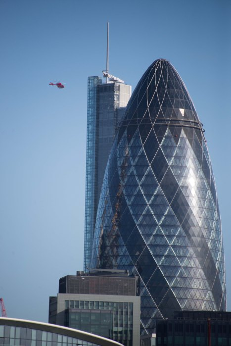 View of the Gherkin 30 St Mary Axe with the heron Tower behind and the air ambulance